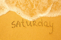 Saturday - written in sand on beach texture Stock Photo