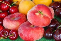 Saturn Peaches (flat Donut peach), apricots, wild and dark cherr Stock Photo