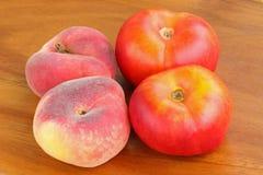 Saturn persikor och plana nektariner på en träbakgrund Arkivfoto