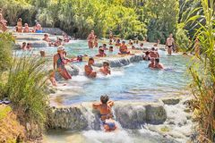 Tourists swimming and relaxing in hot springs at Cascate del Mulino in Saturnia, Tuscany, Italy. stock images