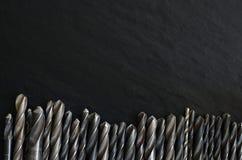 Satz alte Bohrer auf einer dunklen Tabelle Lizenzfreie Stockfotos
