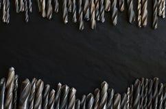 Satz alte Bohrer auf einer dunklen Tabelle Stockfotografie