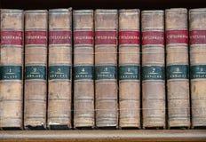 Satz alte Nachschlagbücher auf einem Regal Stockfotos