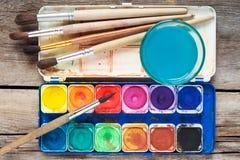 Satz Aquarellfarben, Kunstbürsten und Glas Wasser auf altem Stockfotografie