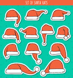 Satz Aufklebers Santa Claus mit 12 des roten Gekritzelhüten Lizenzfreies Stockbild