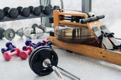Satz Ausrüstung für Gewichtheben und Eignung: Dummköpfe, Barbell und Rudermaschine an der Turnhalle stockfoto