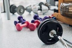 Satz Ausrüstung für Gewichtheben und Eignung: Dummköpfe, Barbell und Rudermaschine an der Turnhalle stockfotografie