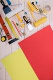 Satz Bauwerkzeuge und farbiges Papier auf Holztisch Stockfotos
