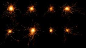 Satz brennende Wunderkerzen auf schwarzem Hintergrund. Stockfotos
