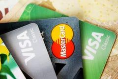Satz bunte Kreditkarten auf dem Währungshintergrund Lizenzfreie Stockfotografie