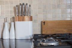 Satz Chefmesser auf Küchenarbeitsplatte nahe bei hackendem Brett und Lizenzfreies Stockfoto
