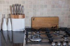 Satz Chefmesser auf Küchenarbeitsplatte nahe bei hackendem Brett und Gasherd stockbild