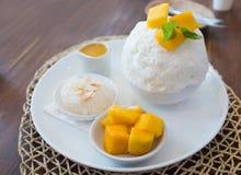 Satz der koreanischen reifen Mango Bingsu, versüßter Kondensmilchnachtisch, klebriger Reis, dienend auf weißer keramischer Platte lizenzfreie stockfotos