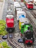 Satz der roter elektrischer Modelleisenbahnlokomotive und -plans mit einer Station und ganze Szene mit Funktionen stockbilder