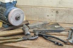 Satz des erfahrenen Arbeiters bearbeitet das Lügen auf einer Holzbank Im Hintergrund mit einem elektrischen Bleistiftspitzer Stockfotografie