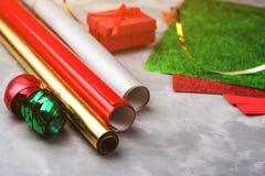 Satz des festlichen dekorativen Papiers und des Bandes für die Verpackung von Geschenkboxen auf grauem strukturiertem Hintergrund Stockfotos