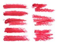 Satz des roten Lippenstiftfleckes lokalisiert auf weißem Hintergrund Befleckte Probe des kosmetischen Produktes Stockbild