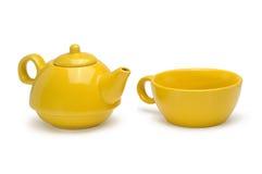 Satz einer gelben keramischen Teekanne und des Bechers auf Weiß Lizenzfreies Stockfoto