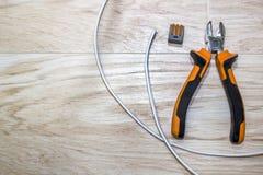 Satz Elektrikerwerkzeuge, eine Spule des Drahtes und Schalter Lizenzfreie Stockfotos
