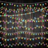 Satz Farbgirlandenlichter Glühende Weihnachtslichter auf hölzernem Hintergrund Schließt 10 festliche Stränge der Vektorbürsten mi Stockfotografie
