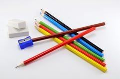 Satz farbige Bleistifte für das Zeichnen mit Radiergummis und Bleistiftspitzer auf weißem Hintergrund Lizenzfreie Stockfotos