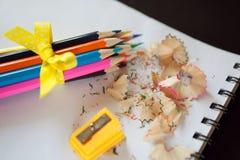 Satz farbige Bleistifte mit Bleistiftspitzer und Schnitzeln Lizenzfreie Stockfotos