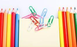 Satz farbige Bleistifte und Büroklammern Stockfotos