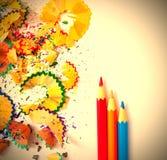 Satz farbige Bleistifte und Schnitzel auf weißem Hintergrund Stockfotos