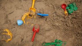 Satz Farbplastikspielwaren auf einem Sand Stockfotografie