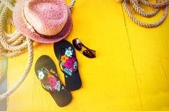 Satz Frau ` s Sachen-Zubehör, zum Jahreszeit-Straw Beach Woman-` s des Hut-Draufsicht-Gelb-Hintergrundes auf den Strand zu setzen Stockbilder