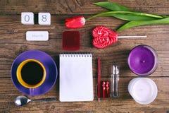 Satz Frauenzubehör rosa Tulip Flower, Lutscher, Datumskalenderblock und zwei cendels auf rustikaler Tabelle für März Lizenzfreie Stockbilder
