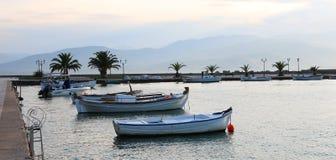 Satz hölzerne Boote der weißen Weinlese auf Meer mit Gebirgshintergrund während des Sonnenuntergangs Lizenzfreie Stockfotos