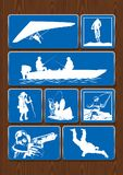 Satz Ikonen von Tätigkeiten im Freien: Ferngläser, Kompass, Wandern, kletternd Ikonen in der blauen Farbe auf hölzernem Hintergru Stockbild