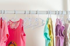 Satz Kleidung für Kinder auf Aufhängern Einkaufen Lizenzfreie Stockfotos