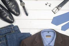 Satz Kleidung und Schuhe der Männer auf hölzernem Hintergrund Stockfotografie