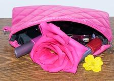Satz Kosmetik in der rosa Tasche mit Blumenrosen Lizenzfreie Stockfotografie