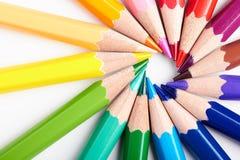 Satz mehrfarbige Bleistifte, die auf runder Bestellung der weißen Tabelle liegen Stockfoto
