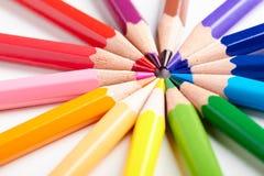 Satz mehrfarbige Bleistifte, die auf runder Bestellung der weißen Tabelle liegen Lizenzfreies Stockbild