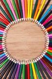 Satz mehrfarbige Bleistifte, die auf runder Bestellung des Holztischs liegen Stockfotos