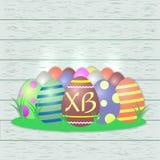 Satz mehrfarbige Ostereier, zentral mit den Buchstaben XB, auf einem hölzernen Beschaffenheitshintergrund stock abbildung