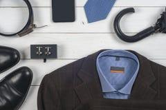 Satz men& x27; s-Kleidung und -schuhe auf hölzernem Hintergrund Lizenzfreie Stockfotografie