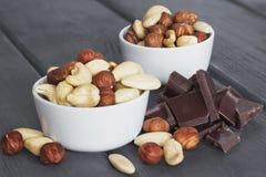 Satz Nüsse in der Schüssel mit Schokolade auf hölzernem Lizenzfreie Stockfotos