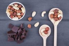 Satz Nüsse in der Schüssel und in der Schokolade auf hölzernem Lizenzfreie Stockfotos