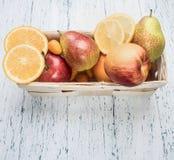 Satz nützliche Früchte, Birnen, Orangen, japanische Orange, Äpfel, in einem weißen Korb auf weißem rustikalem hölzernem Hintergru lizenzfreies stockfoto