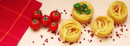 Satz Nudelnester, Basilikum, frische Tomaten und rosa Pfeffer lizenzfreies stockfoto