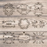 Satz Ornamentrahmen mit Kronen auf Naturholzbeschaffenheit Stockbild