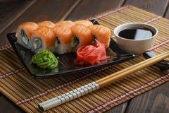 Satz Philadelphia-Sushi-Rolle stellte auf keramische Platte mit Wasabi, Ingwer, Sojasoße und Essstäbchen ein stockfoto