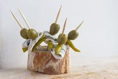 Satz Pintxos Pintxo, Olive, guindilla Pfeffer, Sardelle und Brot auf einem rustikalen Brett, Lebensmittel vom Baskenland Stockbild