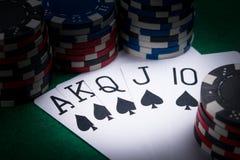 Satz Pokerkarten mit der besten Kombination für einen Spieler in der Dunkelheit eines Kasinos lizenzfreies stockbild