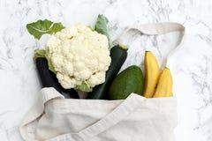 Satz Produkte in einer Baumwolltasche auf einer Marmortabelle, Bananen, avoc lizenzfreie stockfotografie